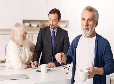 charismatic-peaceful-aged-man-standing-holding-cup-tea-while-his-wife-having-conversation-with-life-insurance-agent-min