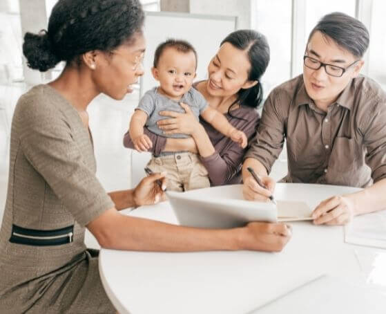 couple-with-kid-signing-life-insurance-policy-in-front-of-insurance-agent