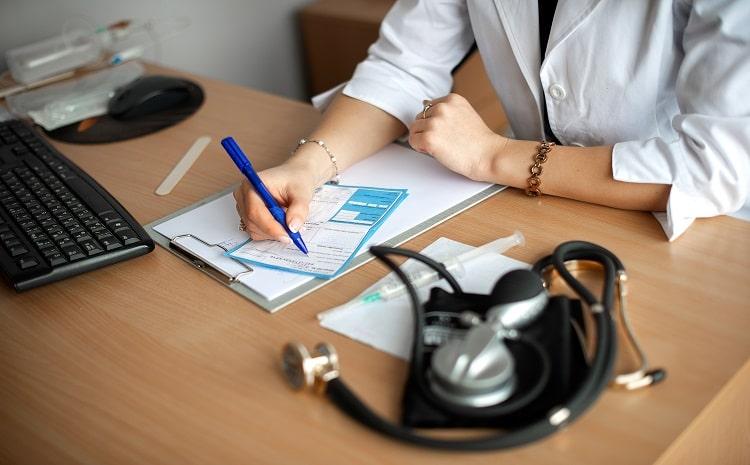 female-doctor-writes-a-prescription-at-his-desk