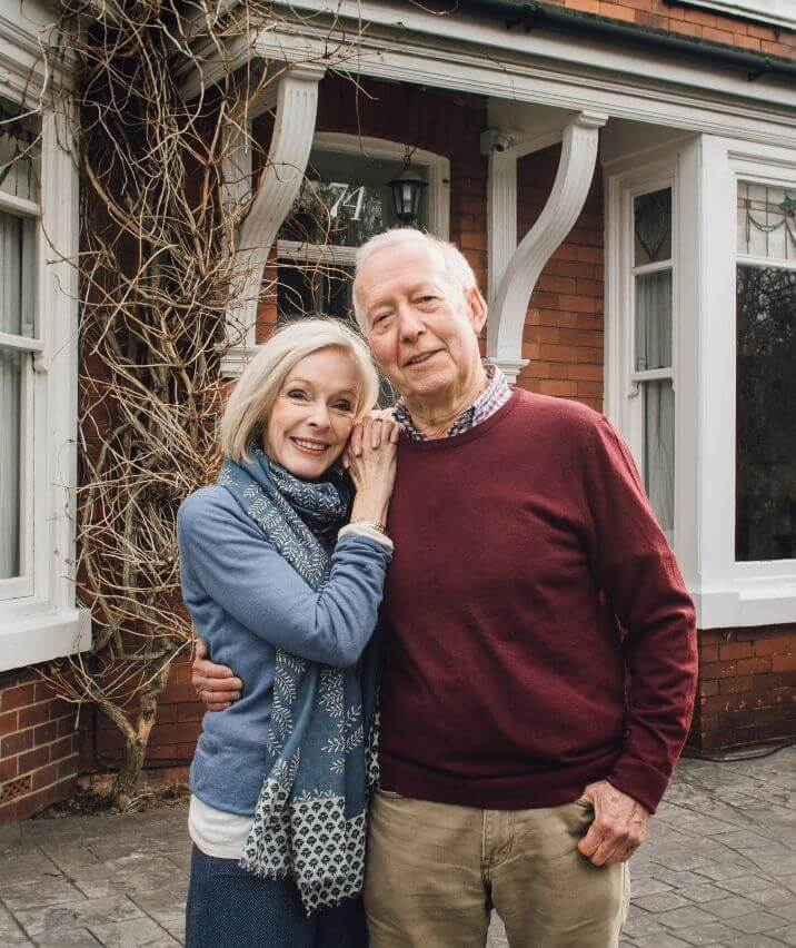 old-couple-standing-front-of-home