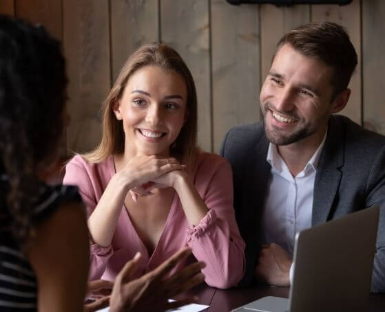 smiling-couple-sitting-in-front-of-insurance-agent