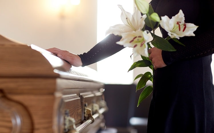 woman-with-lily-flowers-and-coffin-at-funeral
